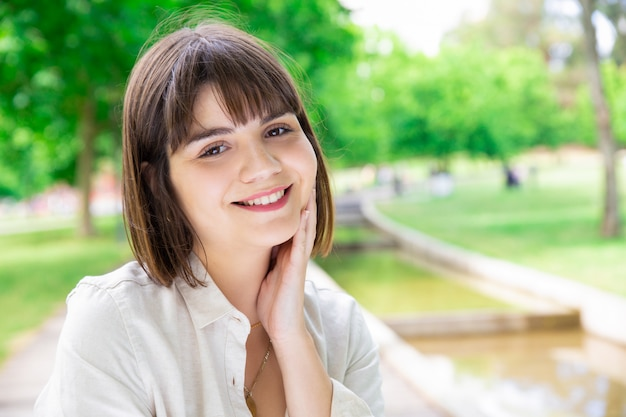 Happy pretty young woman enjoying nature in city park Free Photo