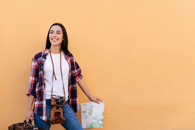 Happy pretty young woman holding bag and map standing near peach wall Free Photo