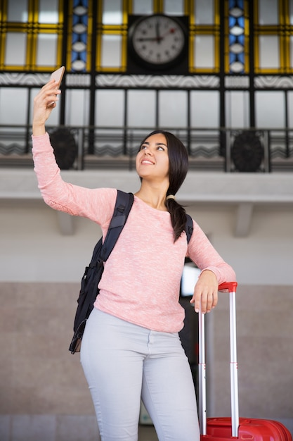 Happy pretty young woman taking selfie photo in station hall Free Photo