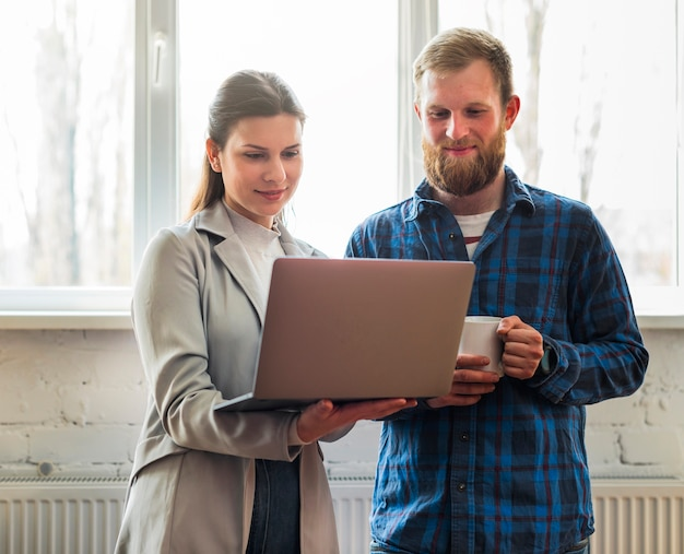 Happy professional businesspeople looking at laptop in office Free Photo