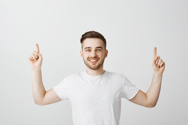 Happy proud guy smiling and pointing fingers up Free Photo