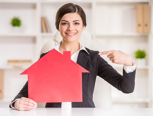 Happy realtor woman is showing home for sale sign. Premium Photo