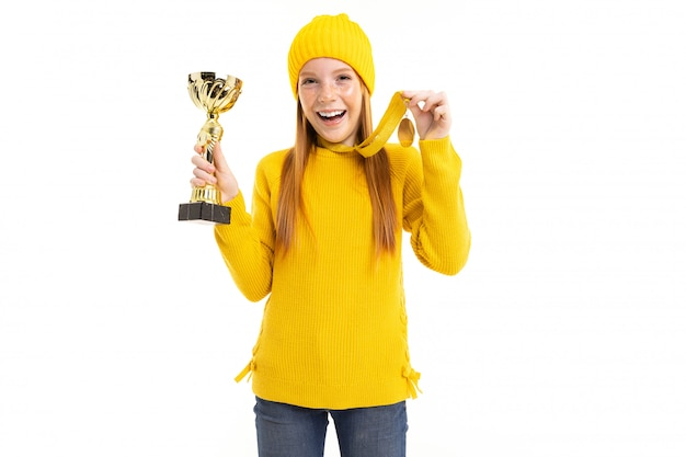 Happy red-haired girl holding a cup and a gold medal over white background Premium Photo
