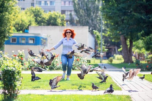 Счастливая рыжеволосая женщина бежит по парку и гонится за голубями Premium Фотографии