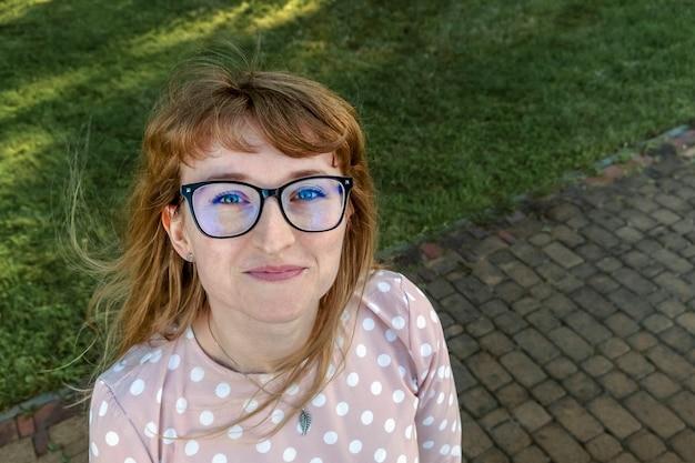 カメラを下から上に見てメガネで幸せな赤毛の女の子 Premium写真