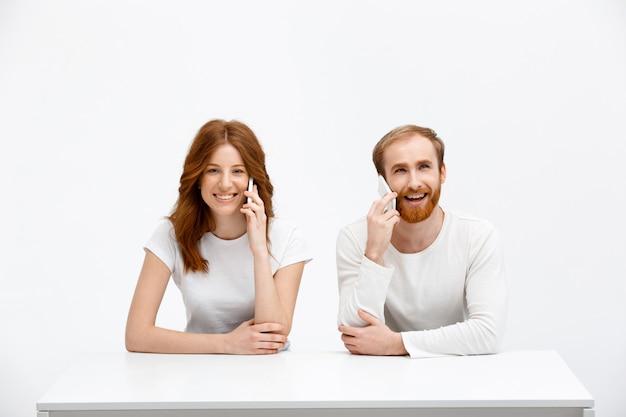 Счастливый рыжий мужчина и женщина разговаривают по мобильному телефону Бесплатные Фотографии