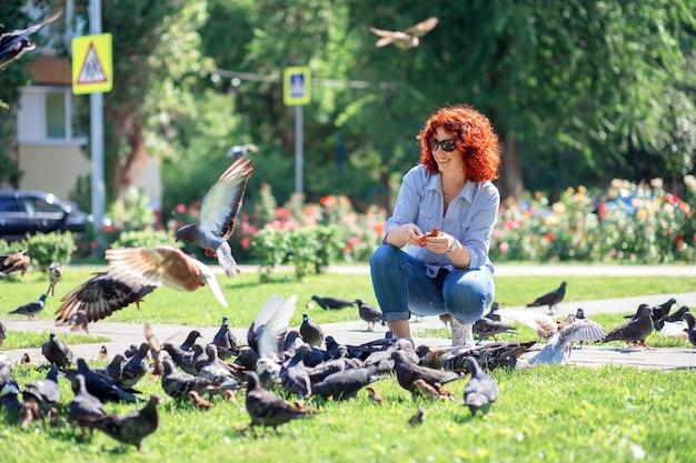 Счастливая рыжая женщина в городском парке кормит голубей хлебом Premium Фотографии