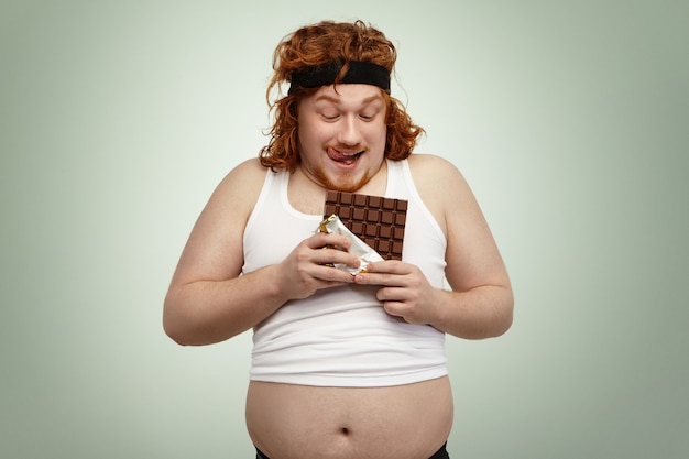 Happy redhead young man in sports wear holding bar of chocolate, about to have some, anticipating its sweet taste after intensive cardio workout in gym. obese overweight male enjoying junk food Free Photo