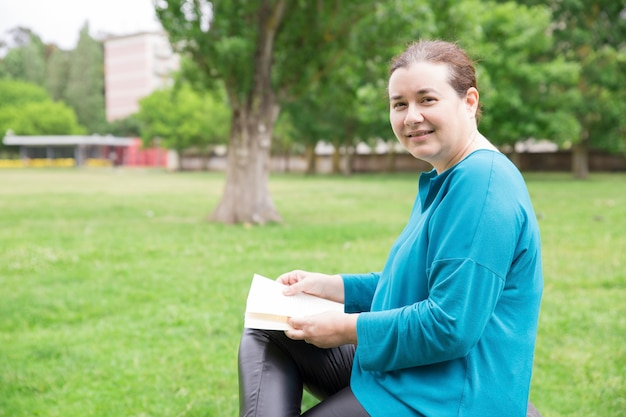 Happy relaxed woman with book enjoying weekend Free Photo