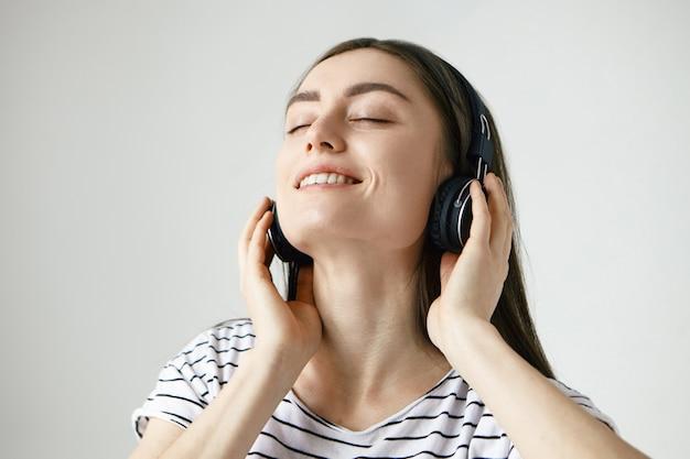 目を閉じて頭を後ろに投げ、ヘッドフォンで音楽を聴き、踊りながら、幸せでリラックスした若い白人女性 無料写真