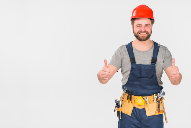 Happy repairman in overall showing thumbs up Free Photo