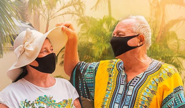 安全のためにマスクを着用して幸せな退職者。引退した老人が老婦人の帽子の下を覗き、妻を見ます。 Premium写真