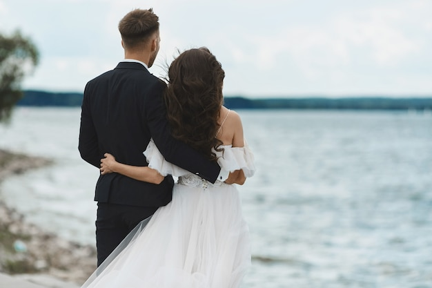 Happy Romantic Wedding Couple In Love Handsome Men In Suit And Young Woman In White Wedding Dress Hugs Together And Posing Back On The Seacoast And Looks At The Horizon Premium