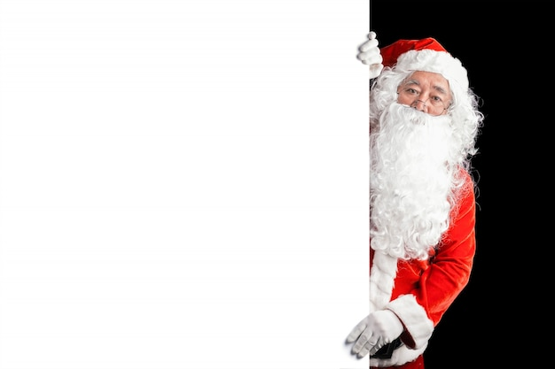 Happy santa claus holding blank advertisement banner background with copy space. smiling santa claus pointing in white blank sign. christmas theme, sales Free Photo