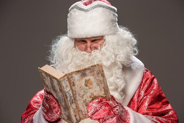 黒の古い本を読んで眼鏡で幸せなサンタクロース 無料写真