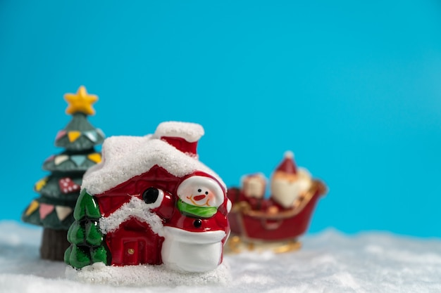 Happy santa claus with gifts box on the snow sled going to snow house. Premium Photo