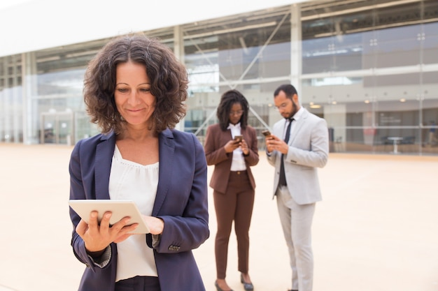 Happy satisfied business woman using tablet outside Free Photo