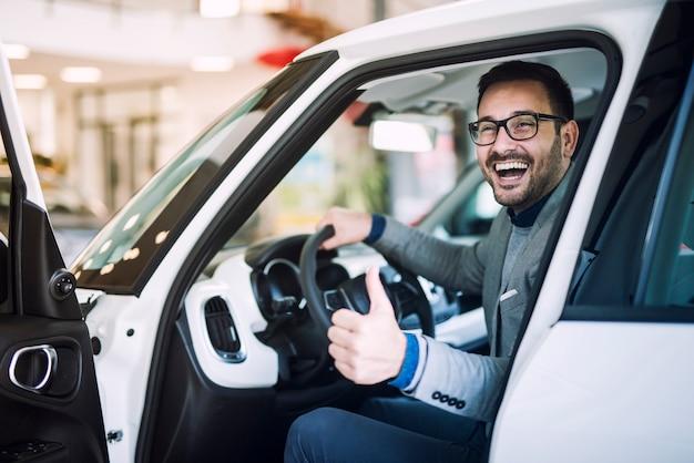 幸せな満足の顧客はちょうど自動車販売店で真新しい車を購入しました 無料写真