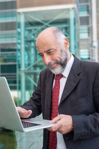 Happy satisfied mature businessman with laptop watching content Free Photo