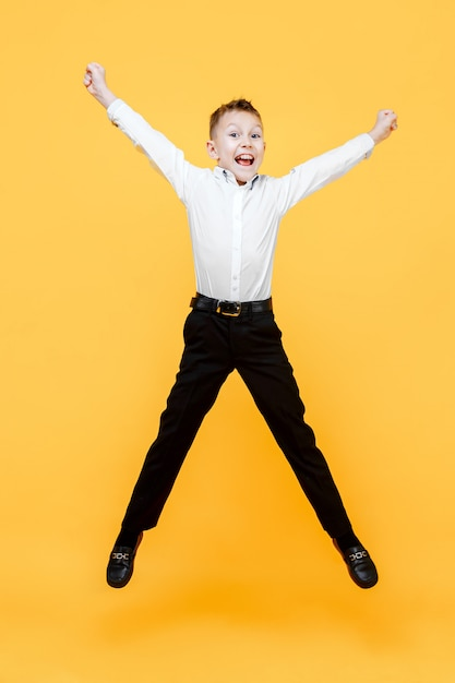 Happy schoolboy jumping for joy. isolated over yellow surface. happiness, activity and child concept. Premium Photo