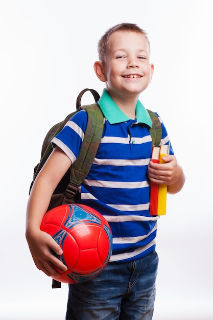 Happy schoolboy with backpack, ball and books isolated on white background Premium Photo
