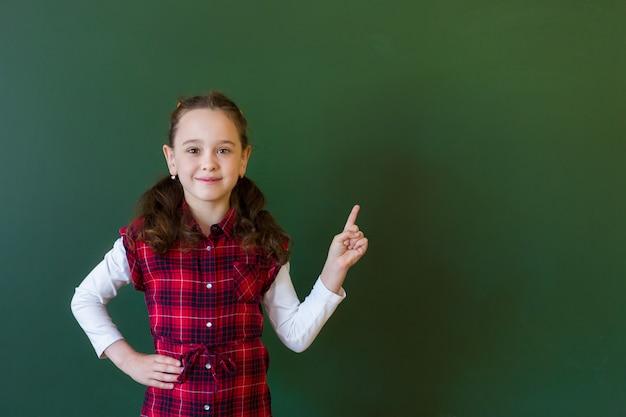 Happy schoolgirl preschool girl in plaid dress standing in class near a green blackboard. concept of school education Premium Photo
