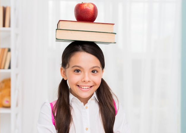 Happy schoolgirl with books and apple on head Free Photo