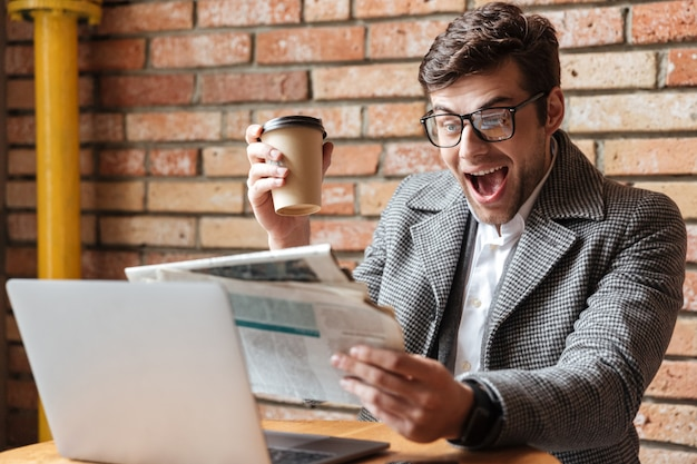 Happy screaming businessman in eyeglasses sitting by the table Free Photo