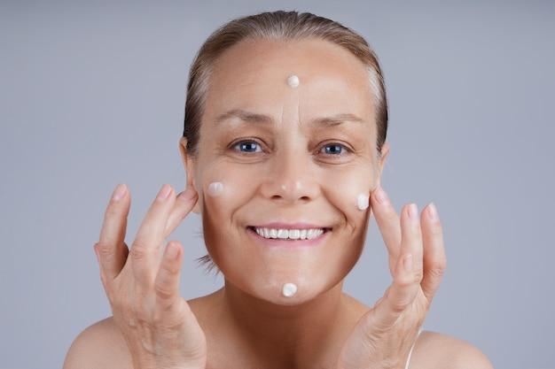 幸せな先輩は彼女の顔に化粧用クリームを塗ります。高齢者のスキンケアに直面します。 Premium写真