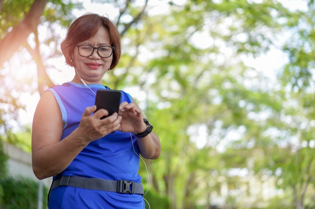 Happy senior asian woman holding smart phone with listening to music Premium Photo