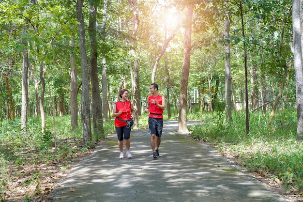 Happy senior asian woman with man or personal trainer jogging running in the park Premium Photo
