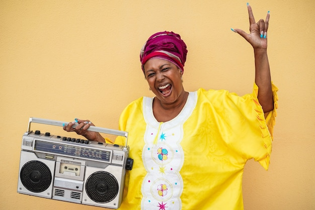 Happy senior black woman with traditional african dress dancing holding boombox stereo - focus on face Premium Photo