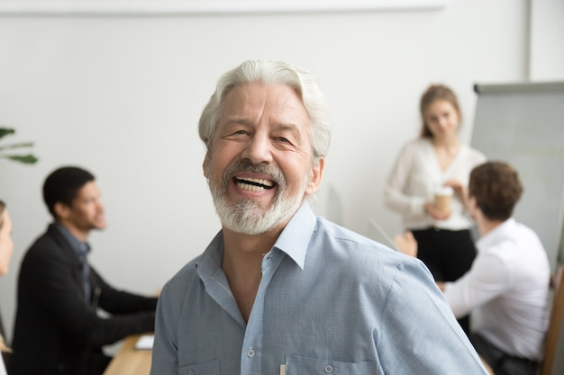 Happy senior businessman laughing looking at camera in office, portrait Free Photo