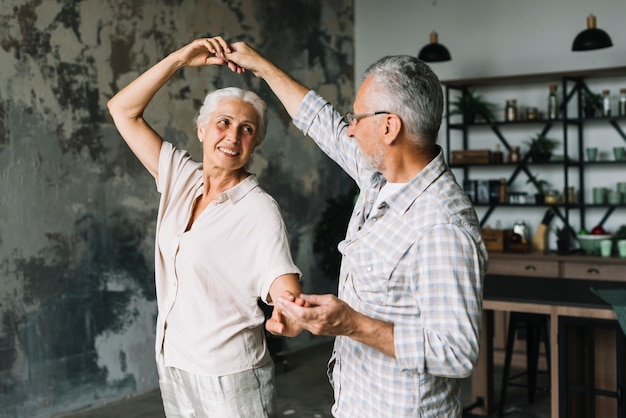 Happy senior couple dancing in the home Free Photo