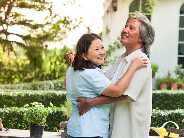 Happy senior couple dancing together in garden home. Premium Photo