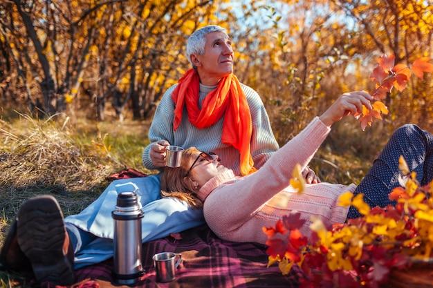 Happy senior couple having tea in autumn forest and enjoying picnic Premium Photo