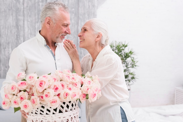 Happy senior couple looking at each other holding basket of roses in hand Free Photo