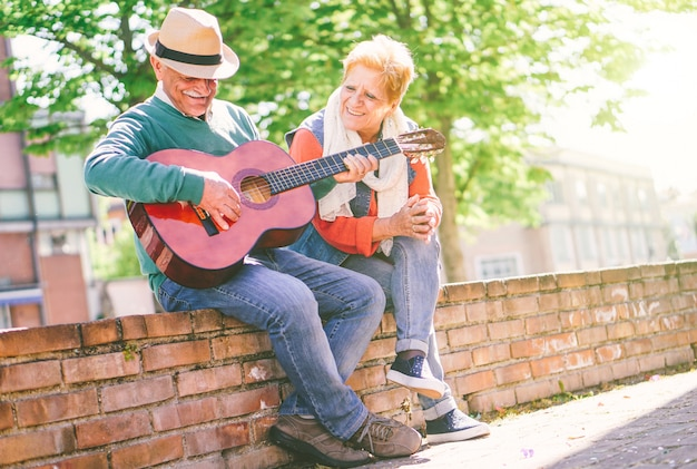 Happy senior couple playing a guitar while sitting outside on a wall on a sunny day Premium Photo
