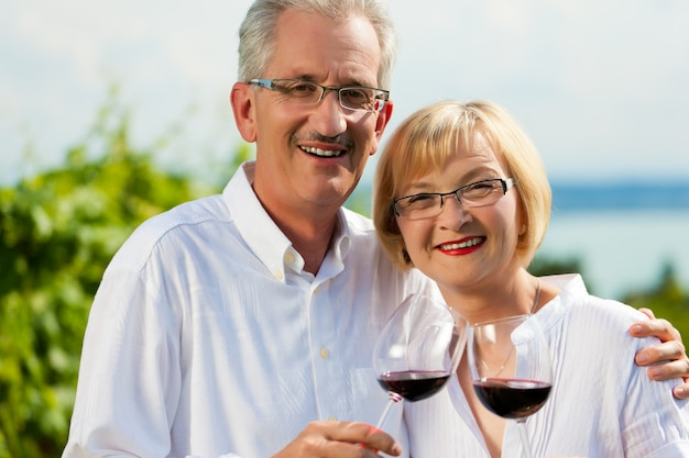 Happy senior couple posing with wine glasses in front of a lake Premium Photo