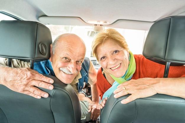 Happy senior couple ready for driving car on journey trip Premium Photo