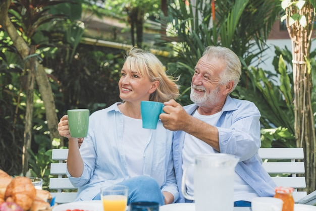 Happy senior couple relaxing drinking coffee in the morning at home garden Premium Photo