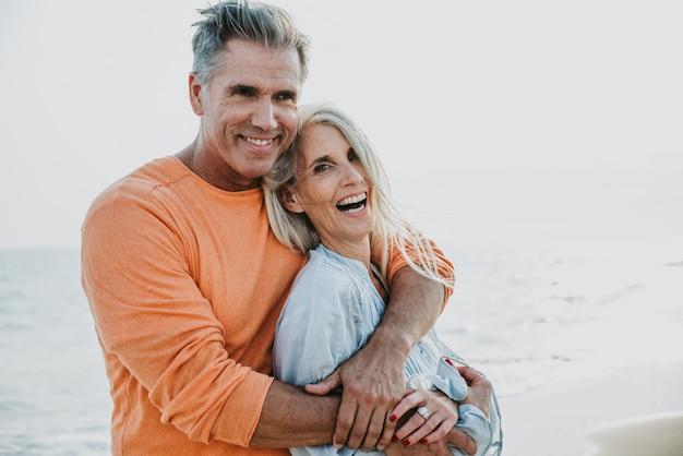 ビーチで過ごす幸せな先輩カップル。愛、老後、人についての概念 Premium写真