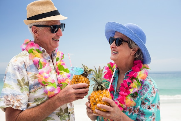 Happy senior couple wearing a garland and holding pineapple cocktail Premium Photo