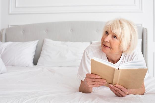 Happy senior holding a book Free Photo