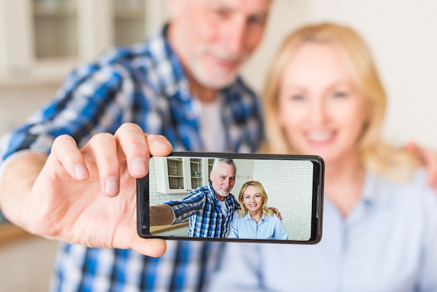 Happy senior husband and wife are making selfie on mobile phone in kitchen Free Photo