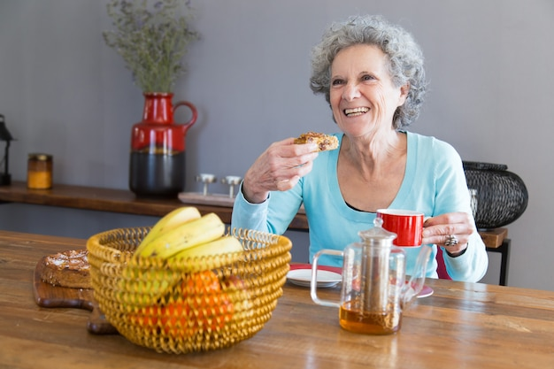 Happy senior lady enjoying dessert Free Photo