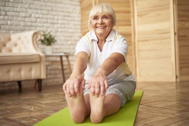 Happy senior lady touches toes workout at home. Premium Photo