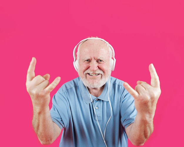 Happy senior likes rock and roll music Free Photo