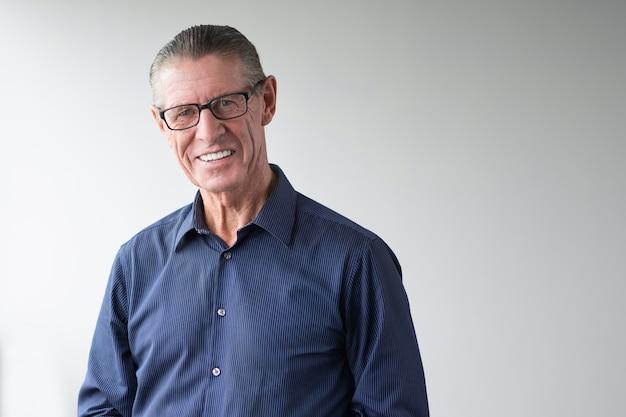Happy senior man wearing glasses smiling at camera Free Photo