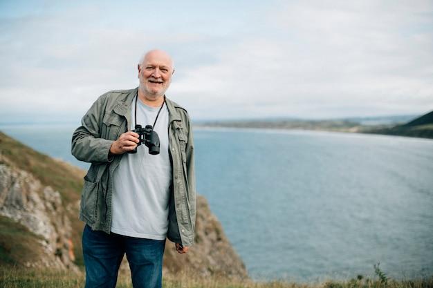 Happy senior man with a pair of binoculars Premium Photo
